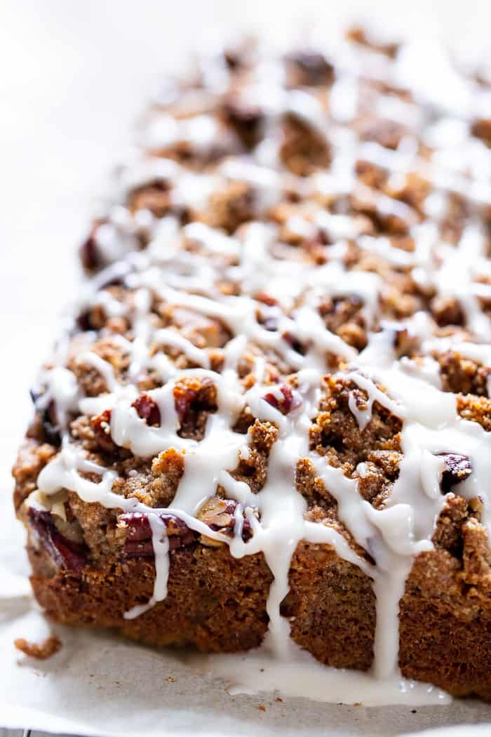 a brown cake loaf with crumbly topping and white frosting drizzled generously overtop