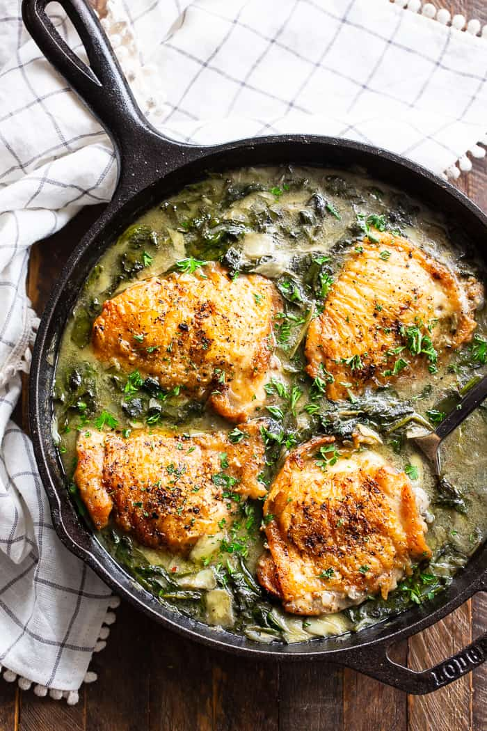 four cooked chicken thighs in a spinach artichoke mixture in a cast iron skillet