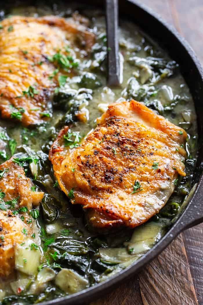 closeup shot of a cooked chicken thigh over spinach and artichokes in a cast iron skillet