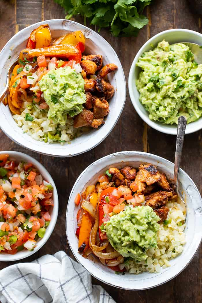 These Paleo Chicken Burrito Bowl are packed with tons of flavor and goodies!  Bite size seasoned chicken thighs, zesty cauliflower rice, pepper and onions plus and easy guac make these bowls healthy, filling, and a family favorite.  Whole30 and keto friendly.
