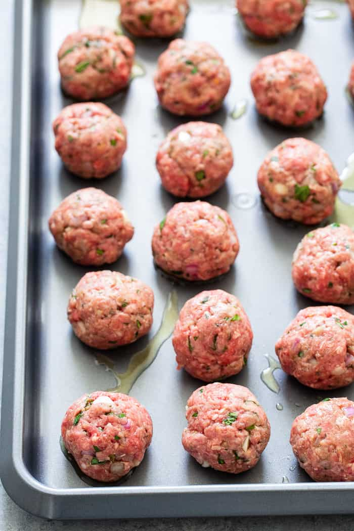 These easy greek meatballs are perfectly flavorful and delicious dipped in a dairy-free paleo Tzatziki sauce!  Great as an appetizer or as part of a meal over a greek salad. Paleo, Whole30, and keto friendly.