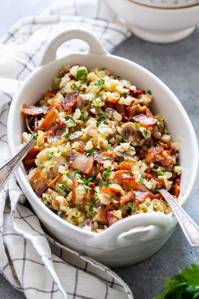 This cauliflower risotto is super easy to make, packed with flavor and savory goodies!  Bacon, mushrooms, and a creamy sauce make this side dish one you'll want again and again!  It's dairy-free, paleo, keto friendly and Whole30 compliant.