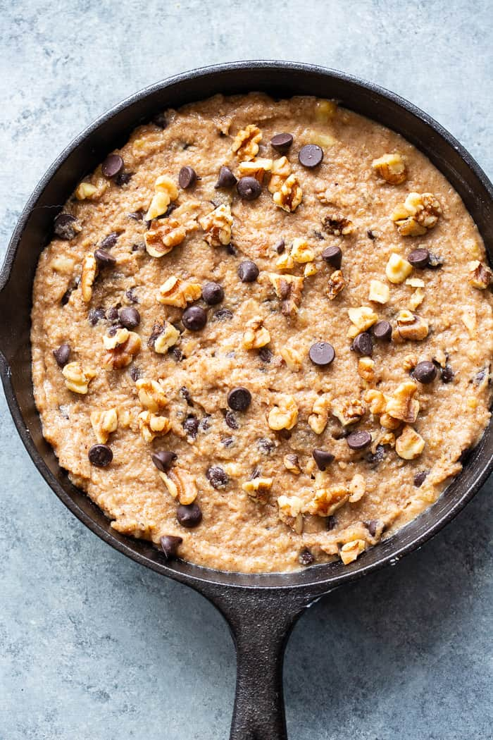 This banana gooey chocolate chip skillet cookie is a dessert that's heathy enough for breakfast!  It's loaded with healthy fats, sweetened with bananas and unrefined maple sugar and packed with dark chocolate chips and walnuts.  Gluten-free, grain free, paleo, dairy free, and vegan too!