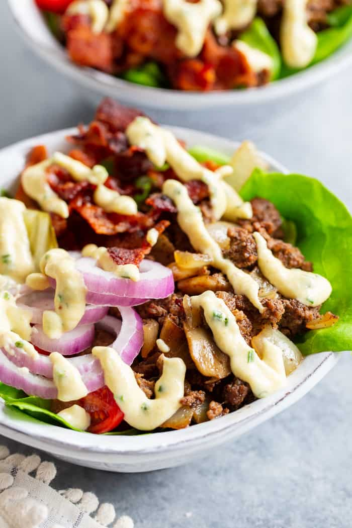 "These deconstructed loaded bacon burger bowls have all the goodies you love in a burger!  Sautéed mushrooms and onions, crispy bacon, pickles, tomatoes, red onion and a ""cheesy"" ranch sauce!  Paleo, Whole30, and keto friendly and seriously delicious!"