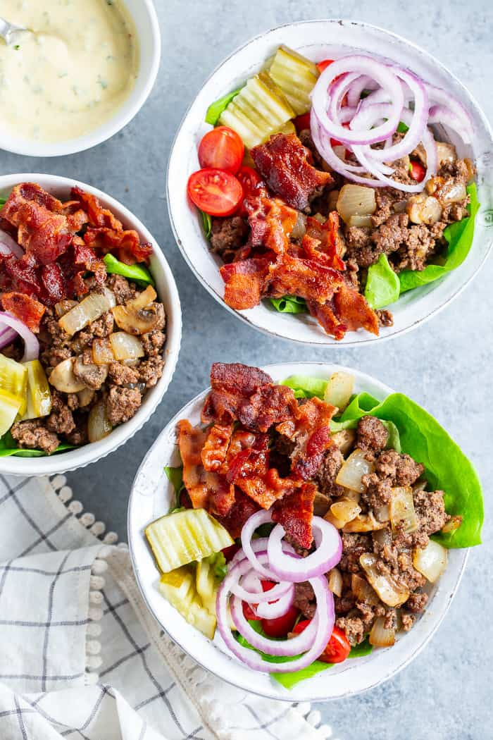 """These deconstructed loaded bacon burger bowls have all the goodies you love in a burger! Sautéed mushrooms and onions, crispy bacon, pickles, tomatoes, red onion and a """"cheesy"""" ranch sauce! Paleo, Whole30, and keto friendly and seriously delicious!"""
