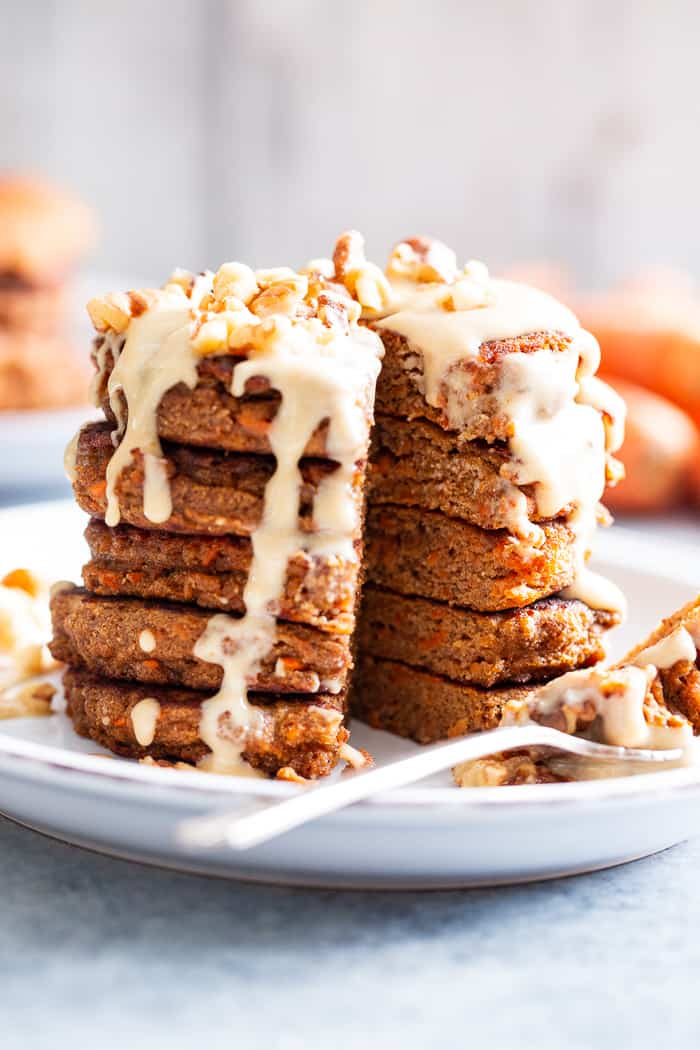 These fluffy, sweet spiced carrot cake pancakes have a dairy-free drizzle that tastes just like a cream cheese icing!  They're made with coconut flour and sweetened with coconut sugar for a healthier take on a Spring breakfast treat.  Gluten-free, dairy-free, refined sugar free, and paleo friendly.