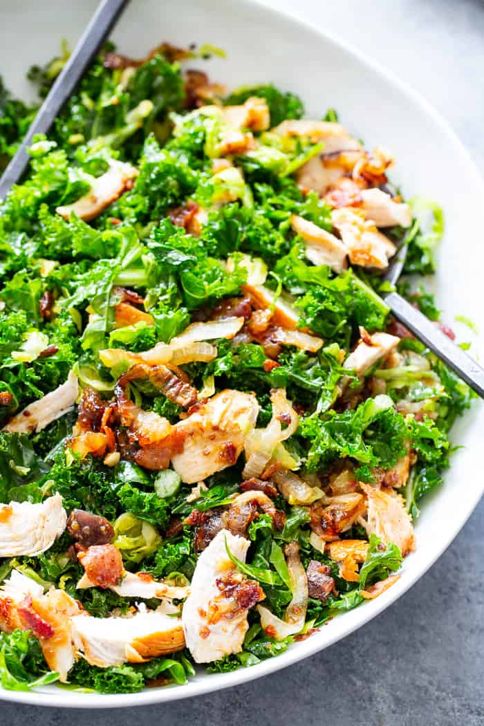This kale salad is packed to the max with goodies!  Kale is tossed with shredded Brussels sprouts, lots of sweet caramelized onions, crispy bacon and grilled chicken plus a super tasty hot bacon dressing.  It's dairy free and paleo with both Whole30 and keto options.
