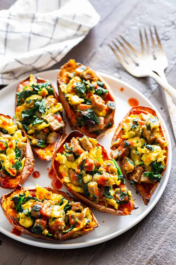 These savory breakfast sweet potato skins are perfect for brunches or breakfast for dinner nights! Crispy skins are loaded with flavor-packed, no sugar added chicken sausage from @JonesDairyFarm, spinach, and eggs and drizzled with hot sauce for extra kick. They're paleo, dairy-free, and Whole30 compliant. #AD #JonesDairyFarm