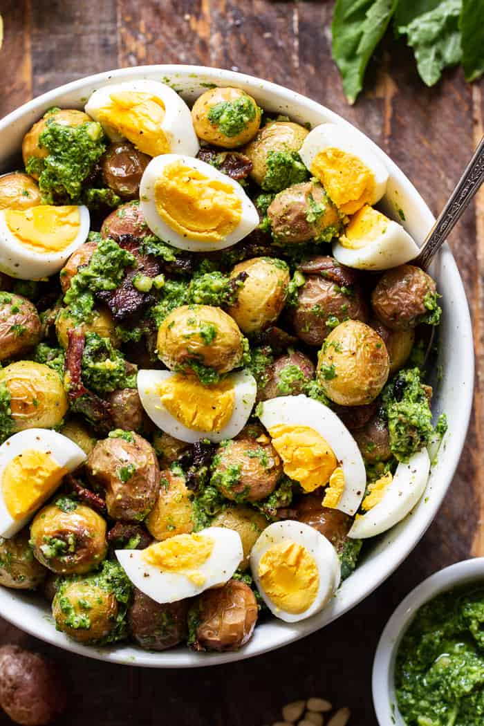 This pesto roasted potato salad is a super tasty twist on your traditional BBQ side dish. Baby potato are roasted to bring out all the flavor and tossed with a dairy-free, Whole30 compliant pesto plus crispy cooked bacon and chopped eggs. It's perfect served at room temperature or slightly warm.