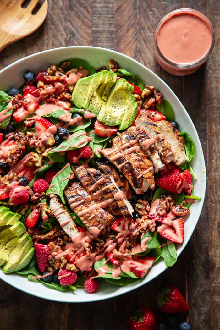 This triple berry grilled chicken salad is packed with flavor with sweet juicy berries, avocado, and a raspberry vinaigrette along with savory grilled chicken, spinach, and walnuts.  It's Paleo, dairy-free, and has a Whole30 friendly option.  Perfect for a light healthy lunch or dinner!