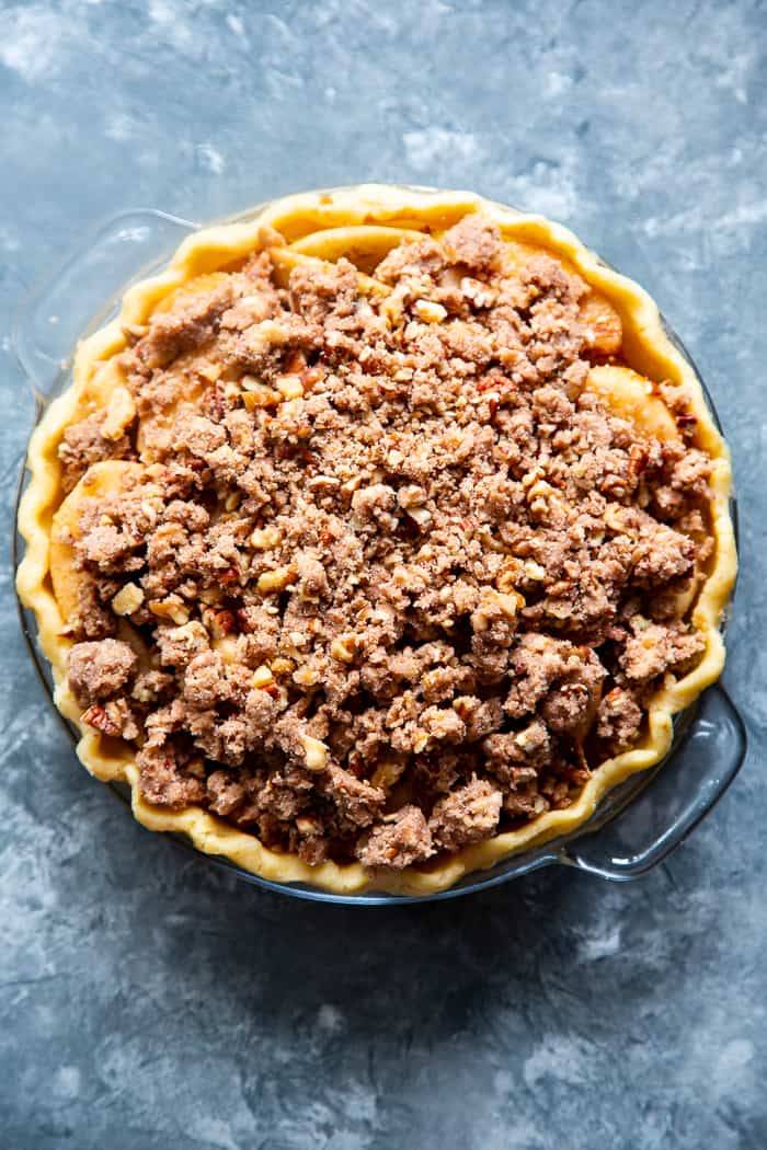 an unbaked apple pie with crumble topping in a glass pie dish over a blue marble background