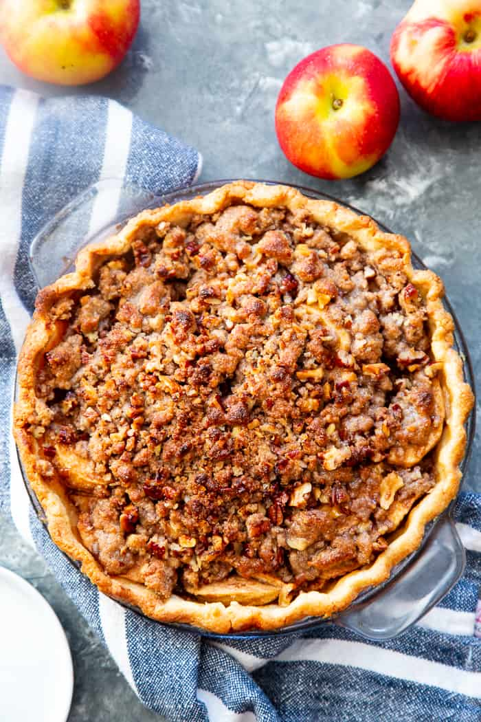 a baked pie with a browned crumble topping with whole red apples to the side and a blue and white striped napkin