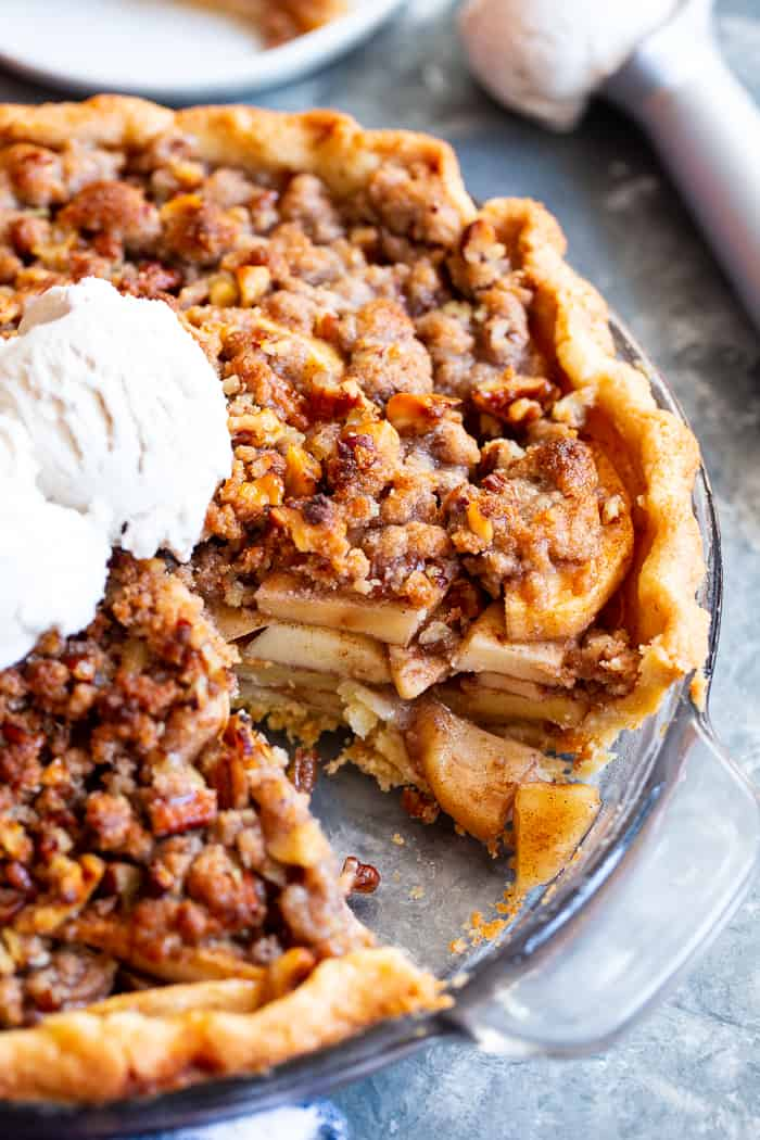 an apple pie with crumble topping and a scoop of ice cream on top