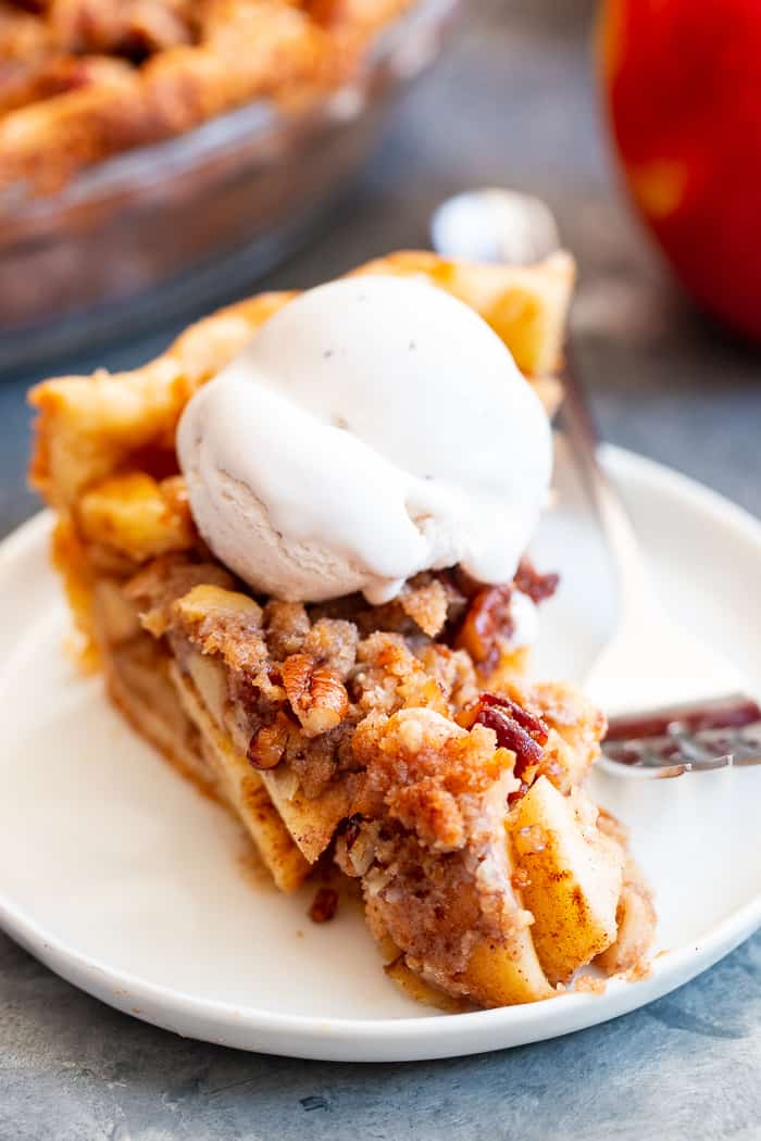 a slice of apple pie with a scoop of white ice cream on top on a white plate