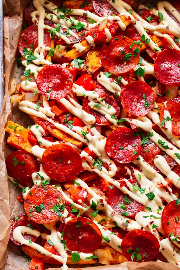 These loaded sweet potato fries have all the toppings to make you feel like you're eating a pepperoni pizza! An easy dairy free cheese sauce, marinara, peppers and onions, and zesty pepperoni make this a fun meal that's just as healthy as it is delicious! Paleo, gluten-free, dairy-free, family friendly.
