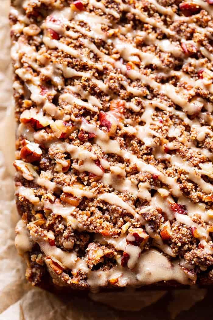 a slab of pumpkin cake with pecan crumble topping and a generous drizzle of a light brown glaze
