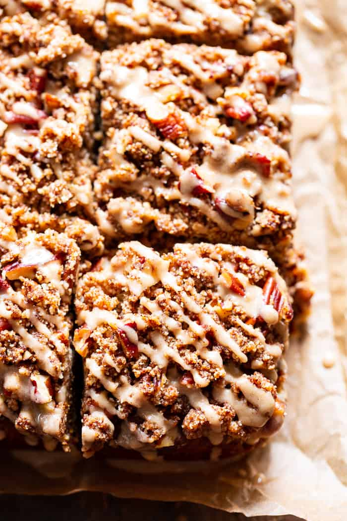 pumpkin cake cut into squares with crumble topping and frosting glaze