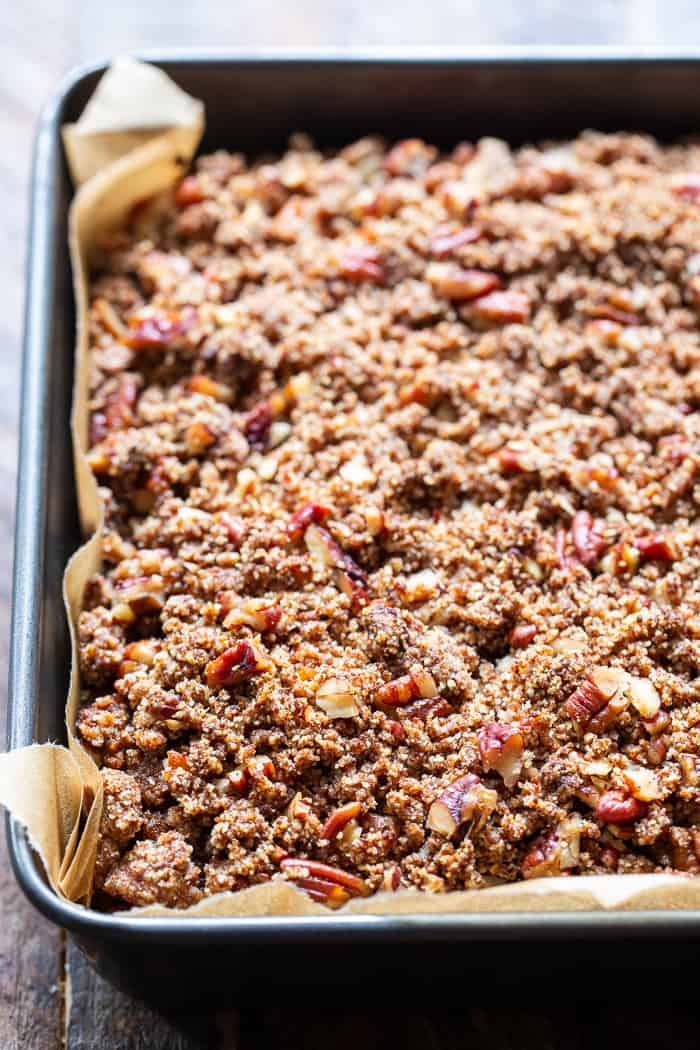 cake with brown chopped pecan crumble topping in a gray square pan