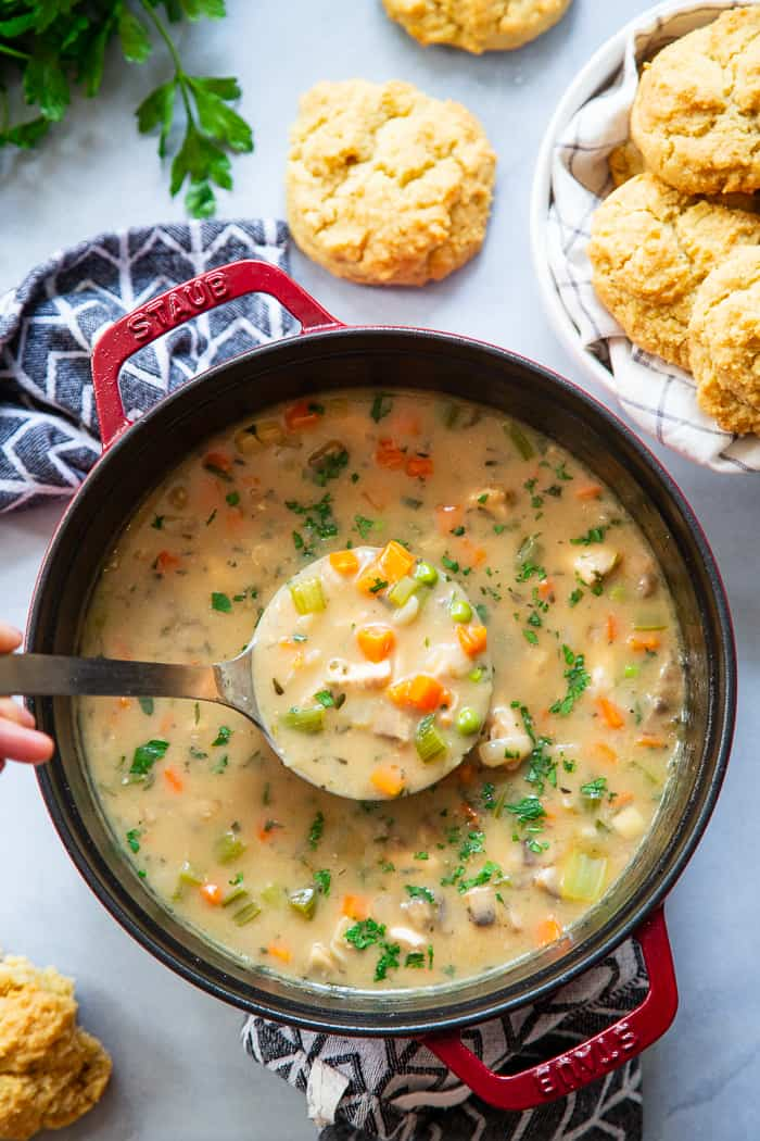 This creamy, cozy and delicious chicken pot pie soup has it all!  A paleo and dairy-free chicken pot pie filling with loads of veggies and savory herbs and the yummiest paleo + low carb biscuits!  The whole family will love this  healthy, hearty soup on cold winter nights.