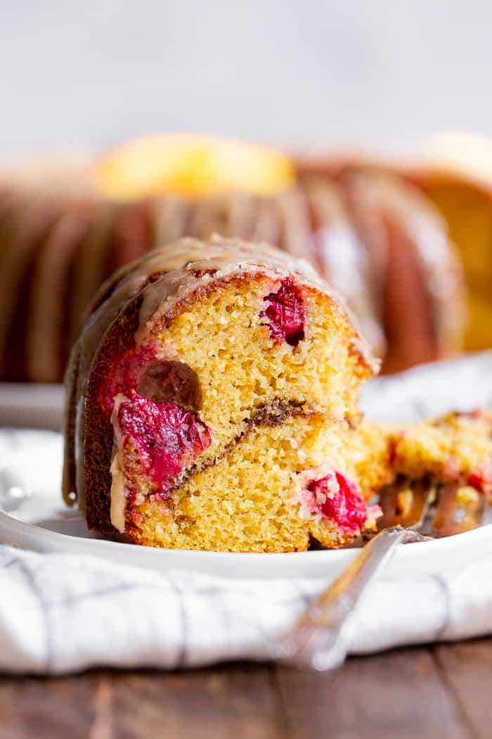 This Paleo Cranberry Orange Bundt Cake is perfectly moist  bursting with sweet orange flavor and tart juice cranberries.  A cinnamon swirl plus sweet maple glaze make this bundt cake a holiday showstopper!  It's gluten-free, grain free, refined sugar free and has a dairy-free option.