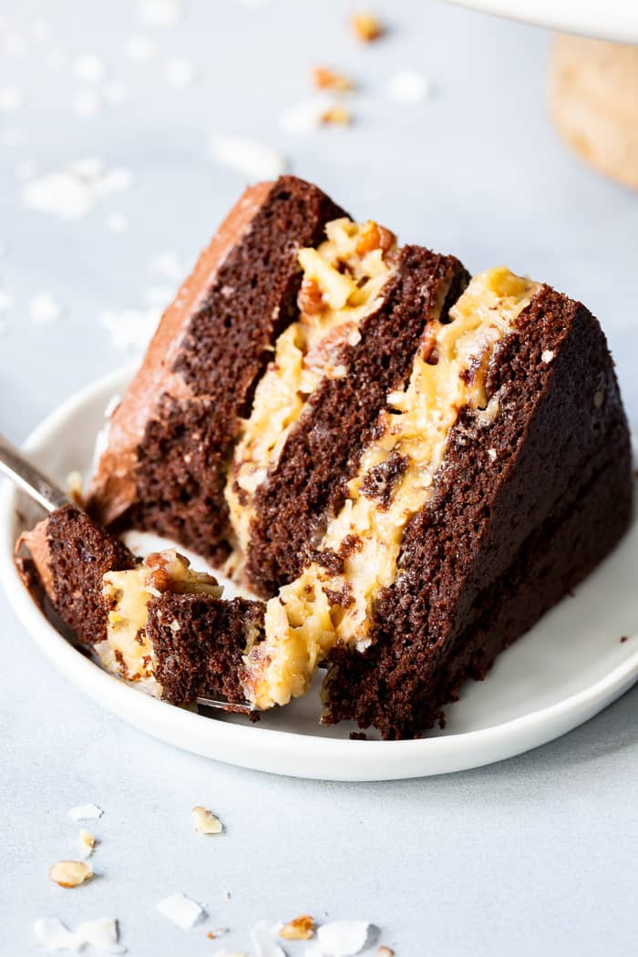 This rich Paleo German Chocolate Cake has a classic coconut pecan filling between tender grain free chocolate cake layers, and is topped with a dairy-free, refined sugar free chocolate frosting.  A showstopper for any gathering, this healthy German Chocolate Cake will become a family favorite!