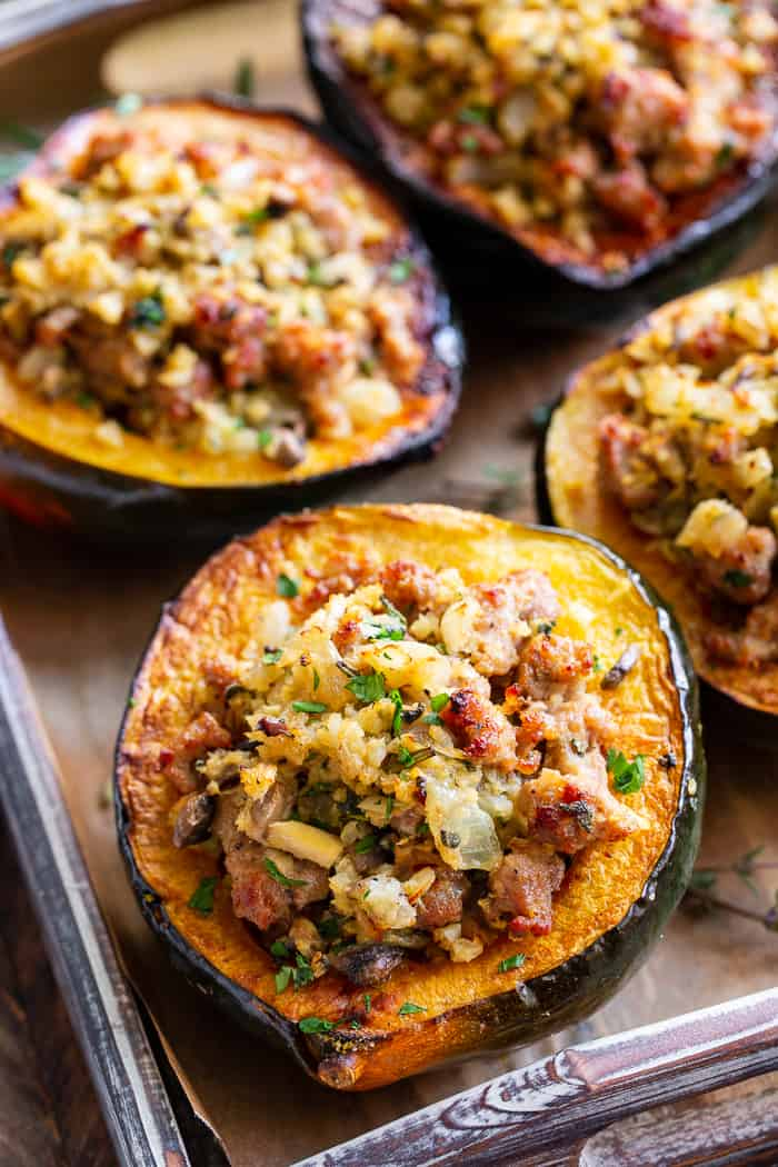 This savory stuffed acorn squash is so delicious it's addicting! A sausage and cauliflower rice stuffing is seasoned with lots of fresh herbs and served toasty in roasted acorn squash bowls. Perfect as a holiday side dish or an anytime meal. Paleo, Whole30, and low in carbs.