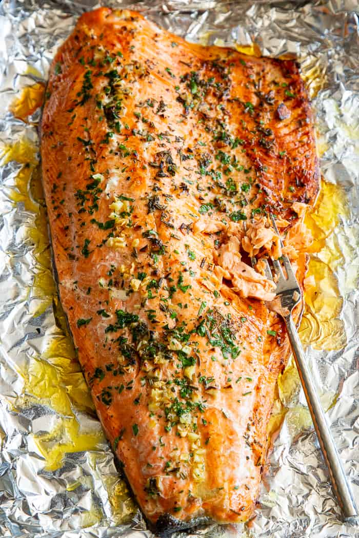 This Baked Salmon in Foil with Garlic, Rosemary and Thyme is easy and out of this world delicious! An simple mix of melted ghee, garlic and fresh herbs (plus a little lemon) give this salmon fillet tons of flavor and a high oven temperature gets the skin a little crispy! It's perfect with all your favorite holiday side dishes and salads, plus quick to throw together.