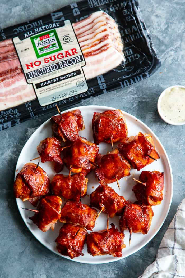 These smoky, savory Bacon Wrapped BBQ Chicken Bites are packed with flavor and easy to make. Zesty chicken bites wrapped in crispy No Sugar All Natural Uncured Hickory Smoked Bacon from @JonesDairyFarm and brushed with lots of Whole30 BBQ sauce. They're gluten-free, dairy-free, with no added sugar – perfect for parties or anytime you're craving a savory snack! #AD
