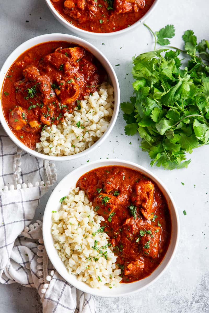 This Instant Pot Indian Butter Chicken is super easy to make and so flavorful!  With just the right amount of spice and a thick creamy tomato sauce, It's perfect over cauliflower rice to keep it Paleo, Whole30, and keto friendly. #cleaneating #whole30 #paleo #keto