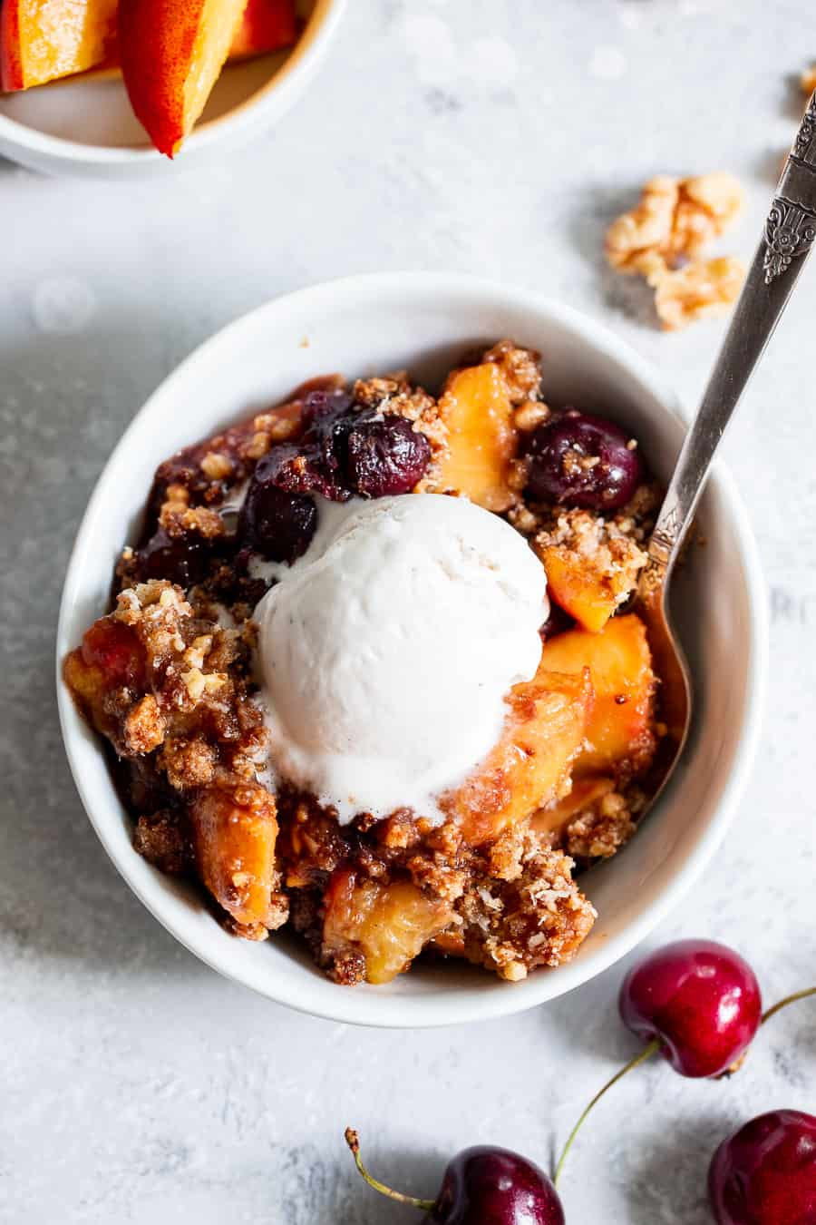 This cherry and peach crisp is irresistibly delicious and easy to make!  A sweet gooey peach and cherry filling is topped with a toasty crumble for a summer dessert that will make everyone come back for seconds.  It's paleo, vegan, gluten-free, dairy-free and refined sugar free. #vegan #paleo #cleaneating #paleodessert
