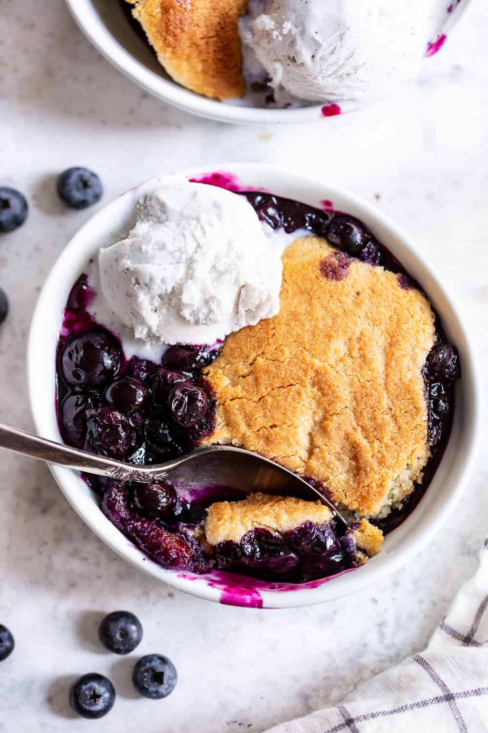 This paleo and vegan blueberry cobbler has quickly become a family favorite!  A sweet gooey blueberry layer is baked with a biscuit cobbler topping that's gluten free, dairy free, and egg free.  It's perfect served with a big scoop of coconut vanilla ice cream or on its own!  Easy to make and the perfect healthy dessert for Spring and Summer. #paleo #vegan #cobbler #glutenfree #paleobaking #cleaneating #glutenfreedessert