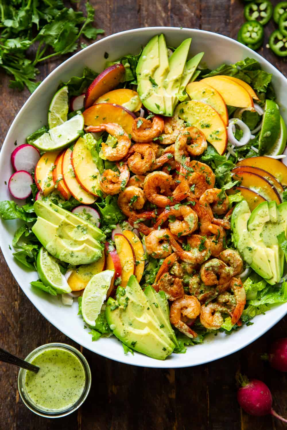 This healthy salad has tons of savory and sweet flavors plus spice! Spicy chipotle shrimp over a fresh summer salad with the most delicious cilantro dressing! Serve it for lunch or dinner over the summer or for your next BBQ. It's easy to throw together and paleo friendly with a Whole30 option. #paleo #cleaneating #shrimp #whole30