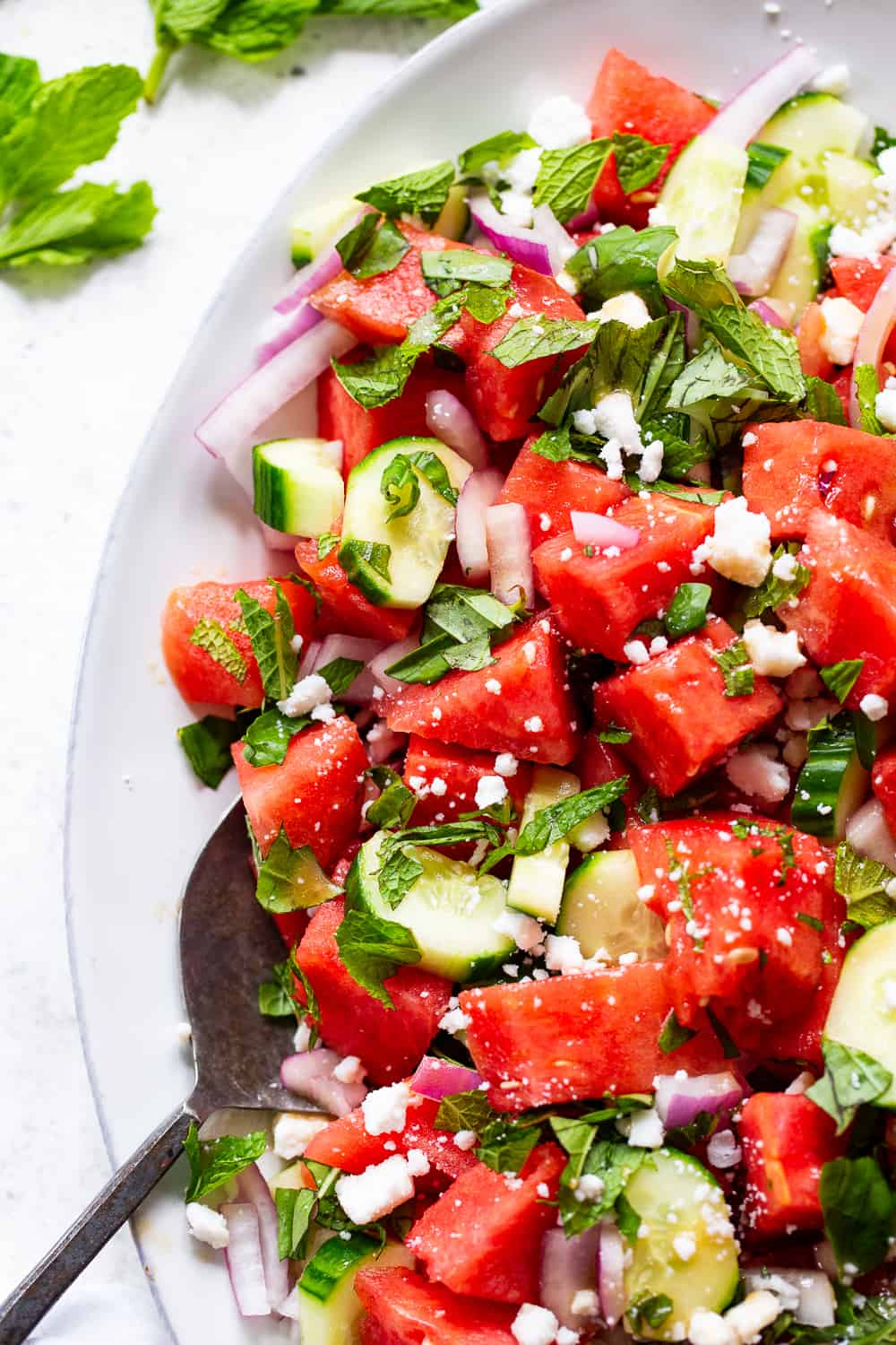 This simple and refreshing watermelon salad has all the flavors you're craving!  Juicy watermelon with cucumber, red onion, basil, mint and dairy free feta cheese tossed in a super simple vinaigrette.  It's healthy, paleo, vegan, and perfect for hot summer BBQs and picnics! #paleo #vegan #cleaneating