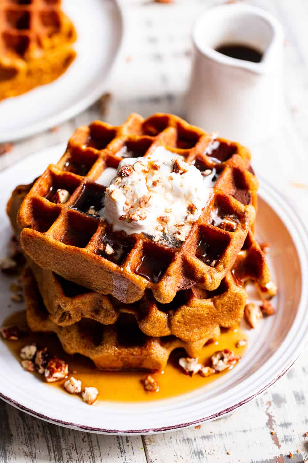 These Paleo Pumpkin Waffles are crisp on the outside, soft inside and filled with warm fall spices. They're just sweet enough to enjoy alone or you can top with all your favorites like maple syrup, coconut whipped cream and chopped pecans. They're kid approved and freeze well so you can enjoy one on the go! Gluten free, dairy free. #paleo #pumpkin #cleaneating #waffles #glutenfree
