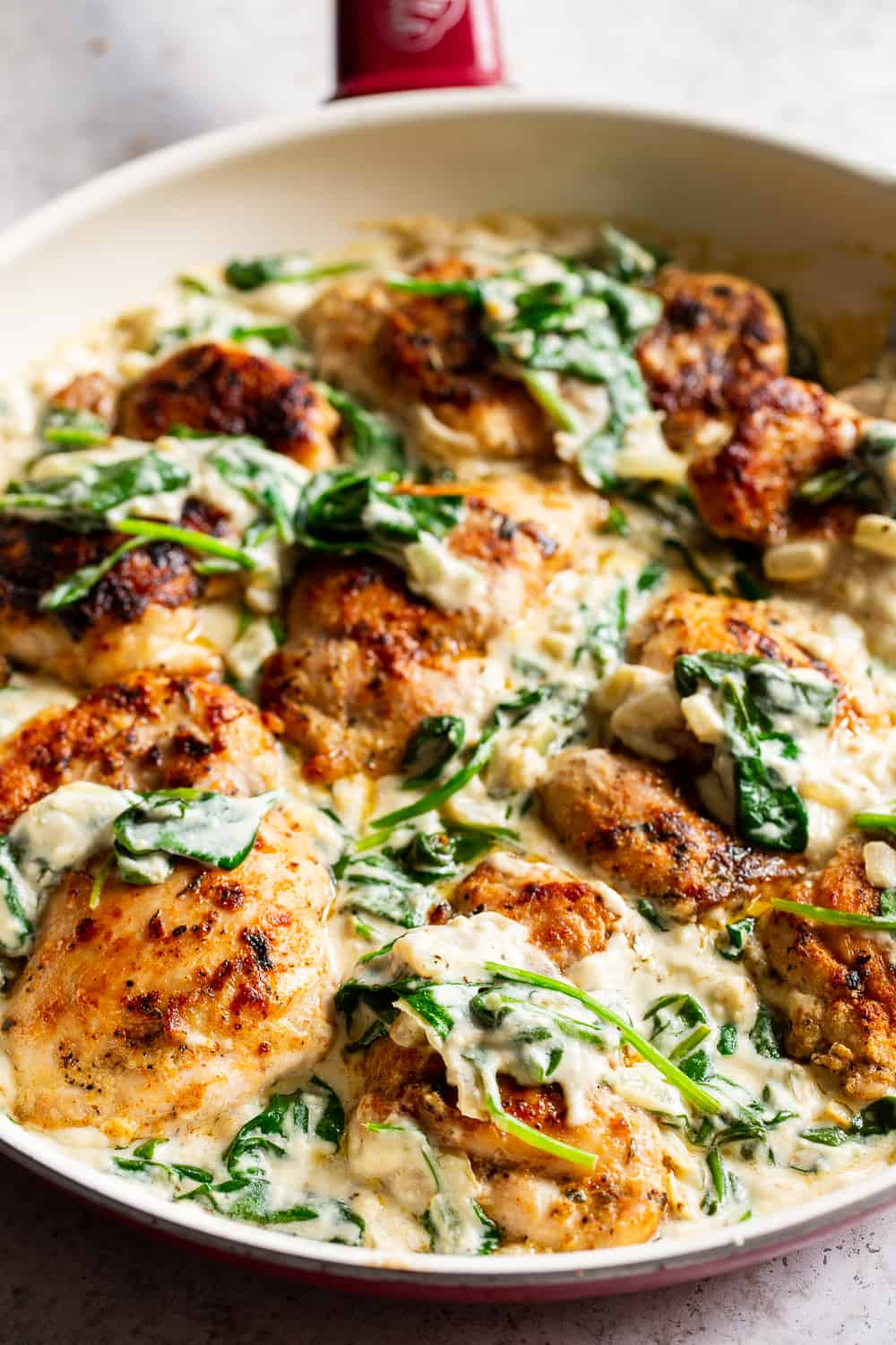 """This one pot creamed spinach chicken is paleo, Whole30 friendly and dairy free but you'd never guess! Juicy seasoned chicken is cooked in one skillet with a creamy, """"cheesy"""" sauce and spinach that's easy and great for weeknights! The leftovers are perfect for lunch the next day too. #paleo #whole30 #keto #cleaneating"""